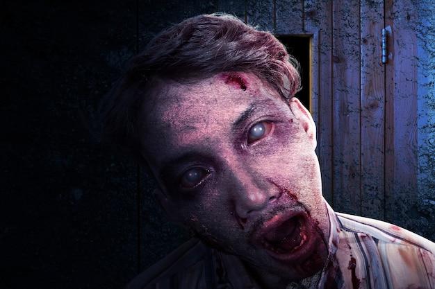廃墟のビルに立っている彼の体に血と傷を負った怖いゾンビ