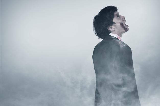 霧の中に立っている彼の体に血と傷を持つ怖いゾンビ