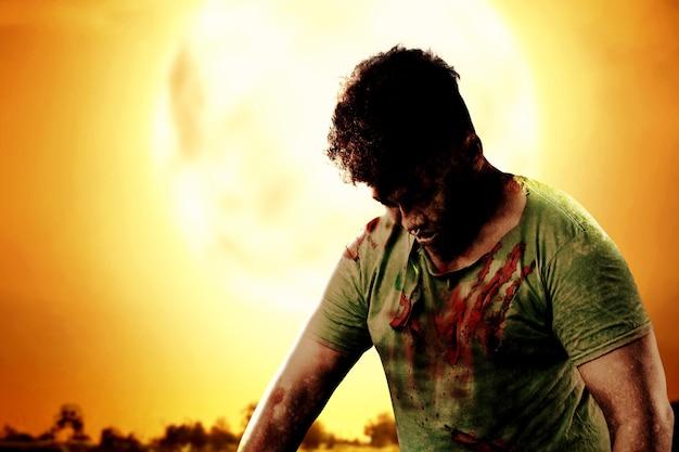 夜景を背景に立っている彼の体に血と傷を持つ怖いゾンビ