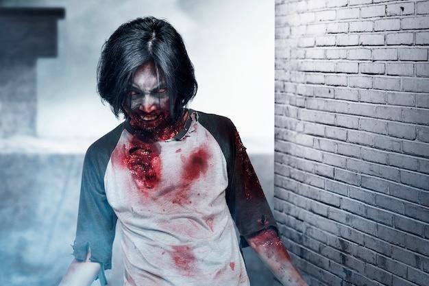 廃墟のビルを歩いている彼の体に血と傷を持つ怖いゾンビ