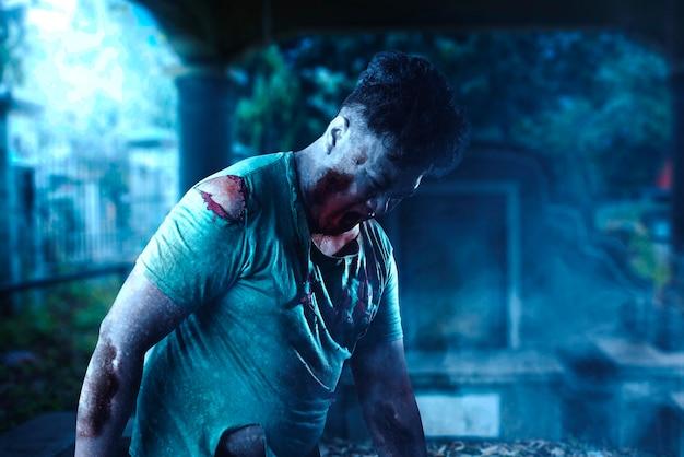 Страшный зомби с кровью и раной на теле гуляет по кладбищу