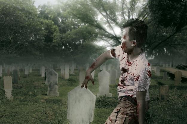 墓地を歩いている彼の体に血と傷を持つ怖いゾンビ
