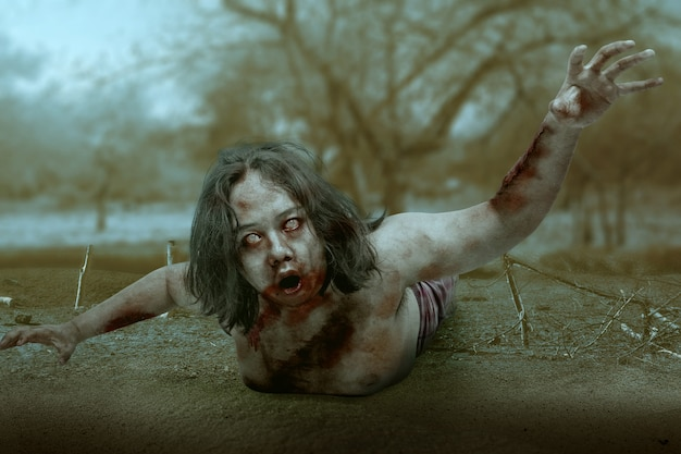 Scary zombie with blood and wound on his body crawling on the field