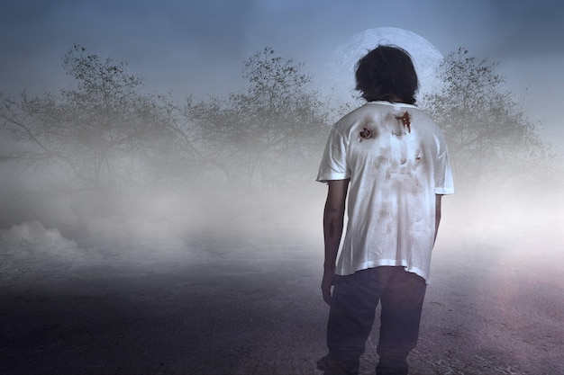 Scary zombie with blood and wound on his body walking on the field