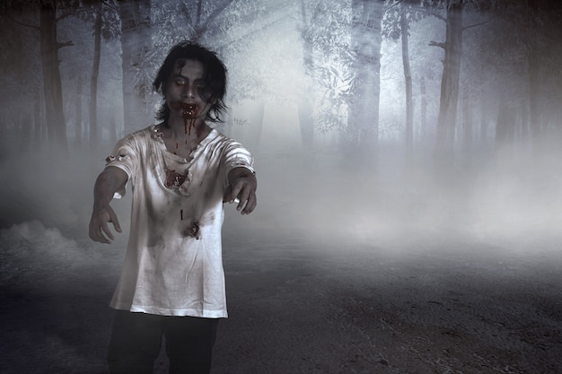 Scary zombie with blood and wound on his body walking on the forest