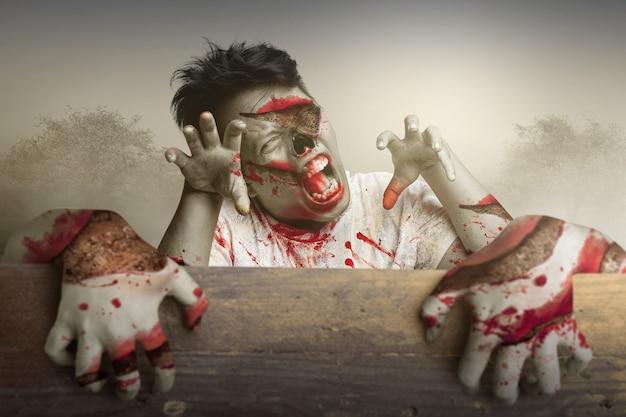 극적인 장면을 배경으로 나무 벽 뒤에 서 있는 무서운 좀비