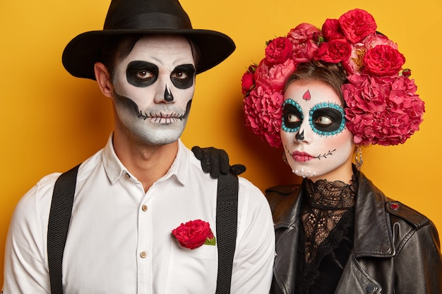 Scarying zombie girl leans at shoulder of man, looks attentively, serious man wears black hat, white shirt with suspenders, prepare for halloween celebration.