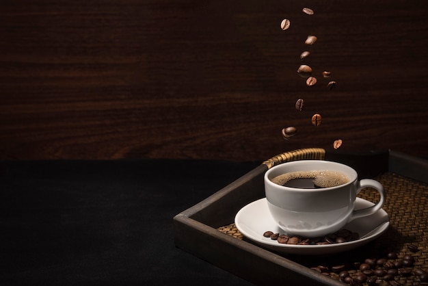 Scatteing coffee beand on coffee cup with coffee beans on bamboo tray