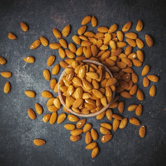 Scattered almonds in a bowl on a grungy grey table. top view.