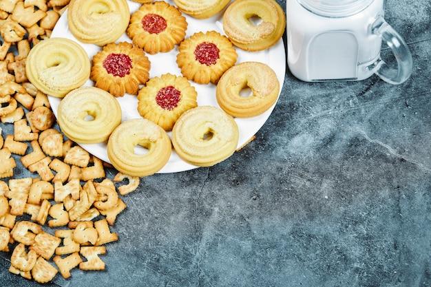 На мраморном столе разбросаны крекеры с алфавитом, тарелка печенья и банка с молоком.
