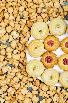 Разбросанные крекеры алфавита и тарелка печенья на синем столе.
