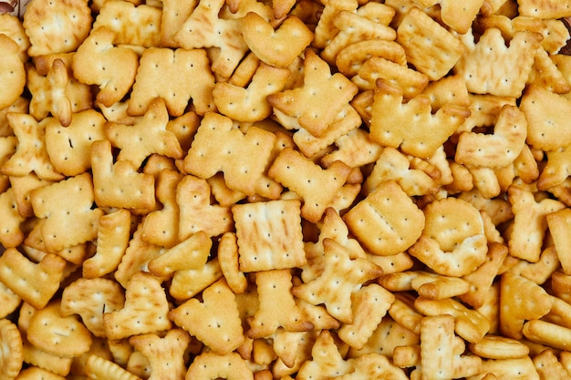 Scattered alphabet crackers on the table. close up.