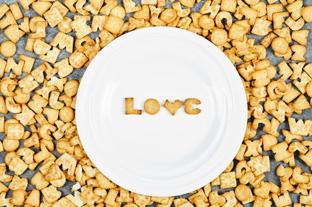 Scattered alphabet crackers and word love spelled with crackers on a white plate.