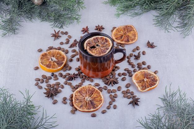 Semi di anice sparsi, fette d'arancia essiccate e una tazza di tè su sfondo bianco.