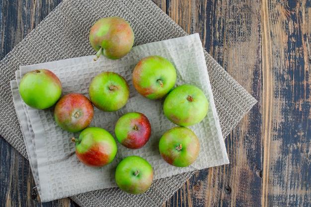 Разбросанные яблоки с кухонным полотенцем на фоне деревянных и салфеток, плоская планировка.