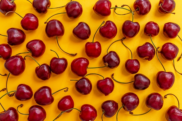 Разбросаны ягоды спелой вишни на ярко-желтом фоне. вид сверху. сезонные витамины.