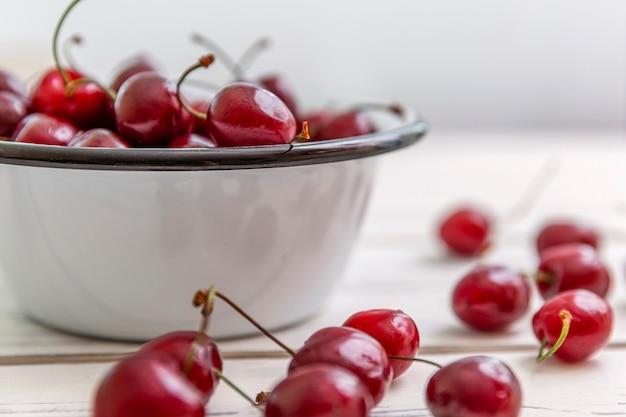 Разбросанные ягоды спелой вишни на светлом деревянном фоне и в миску. вид сбоку. сезонные витамины.