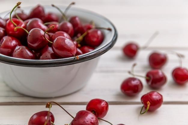 Разбросанные ягоды спелой вишни на светлом деревянном фоне и в миску. вид сверху. сезонные витамины.
