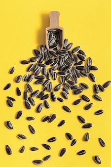 明るい黄色の背景に散在する黒いヒマワリの種と小さな木製のスクープ。収穫期の農業農業。有機健康食品。
