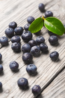 Scattered blueberries on wooden background with leaves