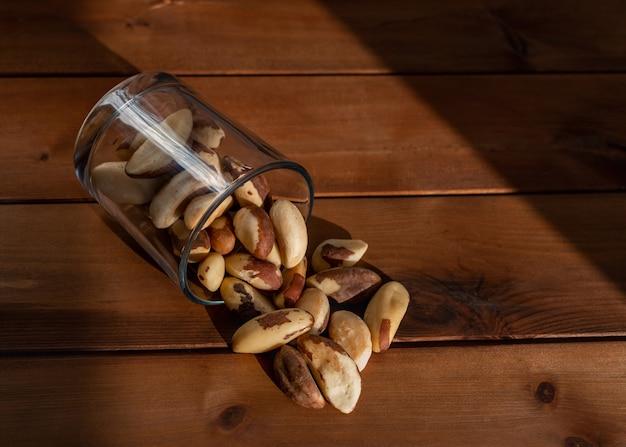 木製のテーブルに自然光の下で散らばったブラジルナッツ。健康食品とおやつ