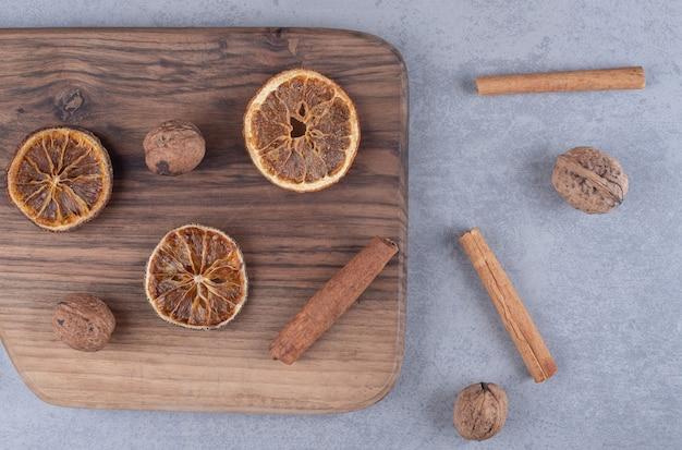 Fascio sparse di fette di limone essiccate, bastoncini di cannella e noci sulla superficie di marmo