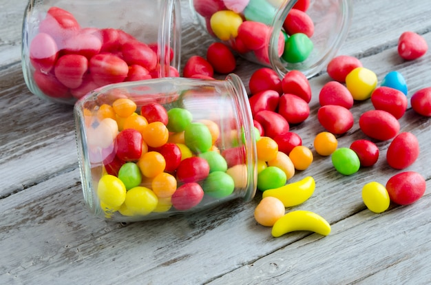 Scattered candies near jar of colorful sweets