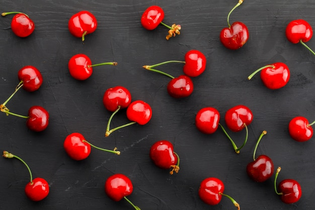 Scattered cherries on a dark grey table. flat lay.