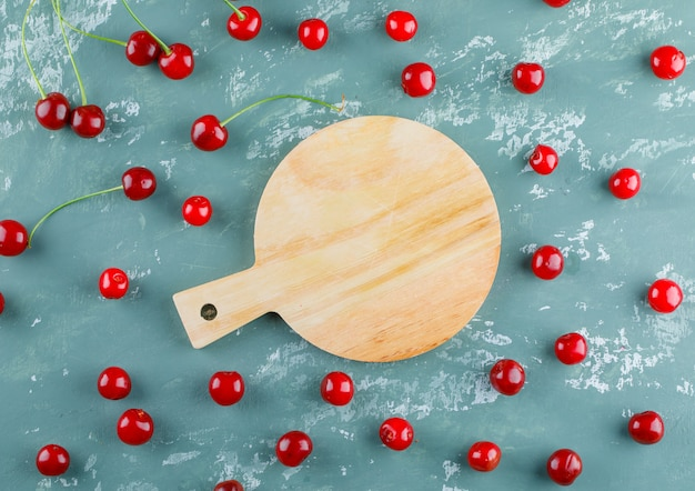 Scattered cherries on plaster and cutting board, flat lay.