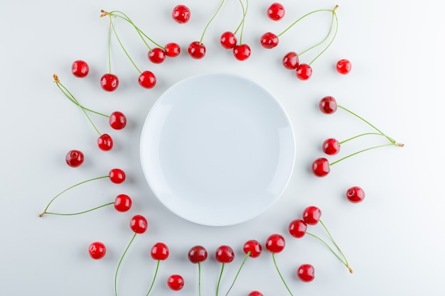Scattered cherries with empty plate, flat lay.