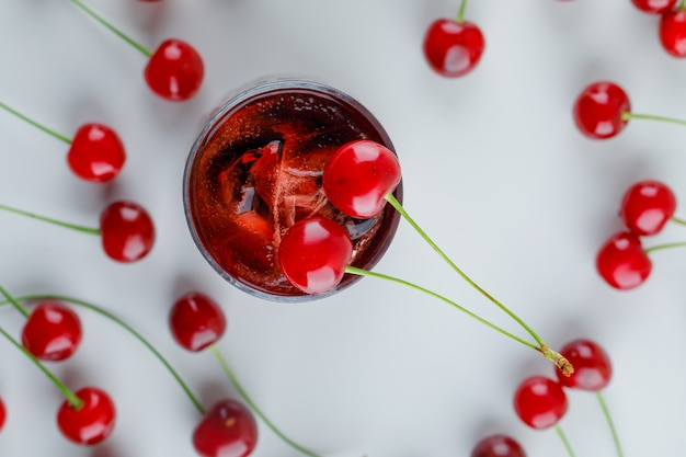 Scattered cherries with icy drink, flat lay.