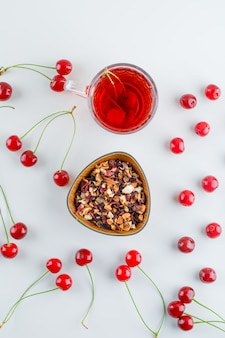 Scattered cherries with tea, dried herbs, top view.