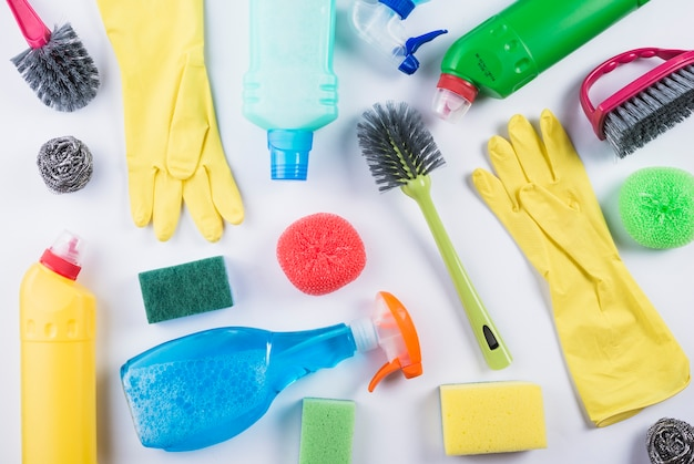 Scattered cleaning products on grey backdrop