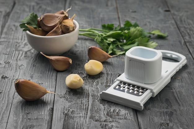 木製のテーブルにニンニク、おろし金、パセリの小枝が散らばっています。キッチンに人気のスパイス。