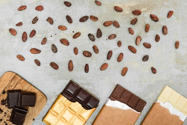 Scattered cocoa beans and different chocolate bars on concrete background