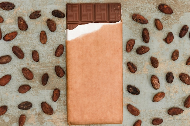 Scattered cocoa beans with chocolate bar on grunge background