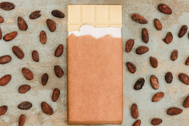 Fave di cacao sparse con la barra di cioccolato bianca sulla priorità bassa del grunge