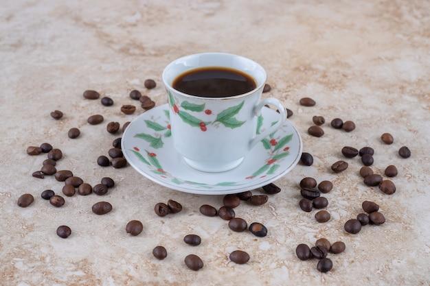 一杯のコーヒーの周りに散らばったコーヒー豆