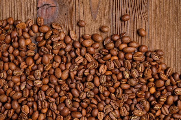 Scattered coffee beans on a burnt wooden background.