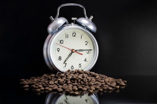 散らばったコーヒー豆、古典的な目覚まし時計。朝のコーヒーの日が始まります。広告のコンセプト。コーヒーを飲む時間。