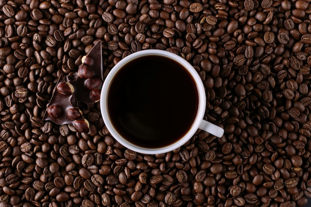 Scattered coffee beans, a cup and black chocolate.
