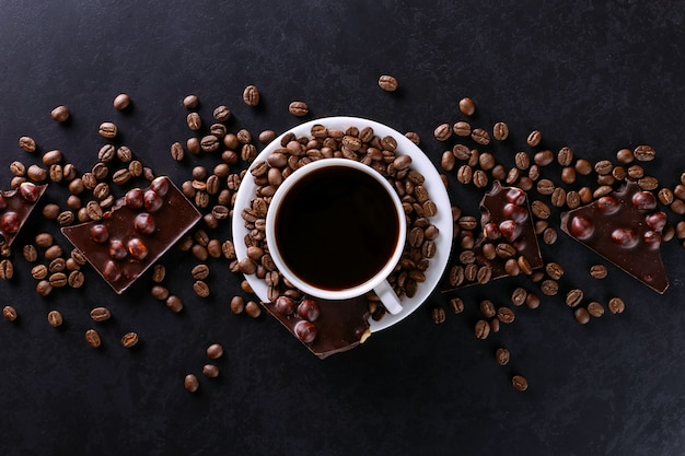 黒い石のテーブルにコーヒーの穀物、カップ、ブラックチョコレートが点在しています。スペースをコピーします。