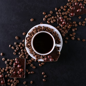 Scattered coffee grains, a cup and black chocolate on a black stone table. copy space.
