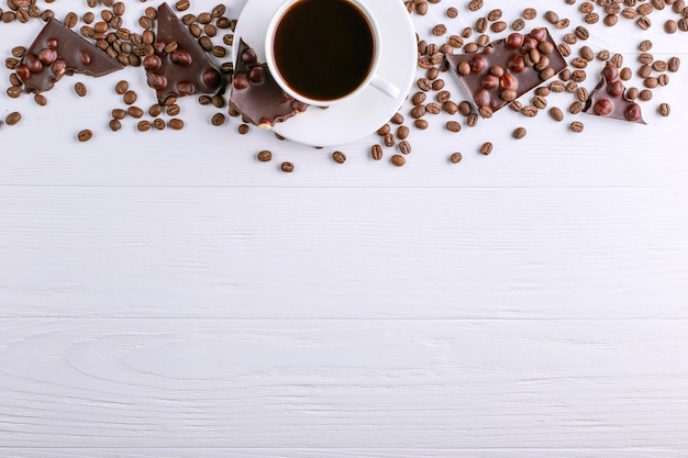 Scattered coffee grains, a cup and black chocolate on a white wooden table. copy space.