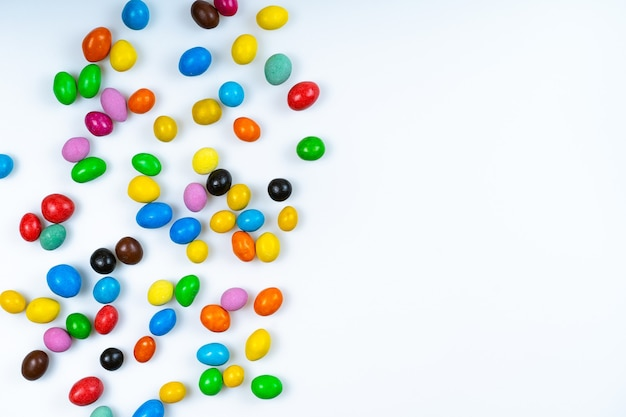 Разбросанные цветные конфеты на белом фоне. яркие круглые конфеты.
