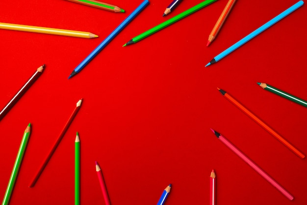 Scattered colorful pencils on red background top view with copy space