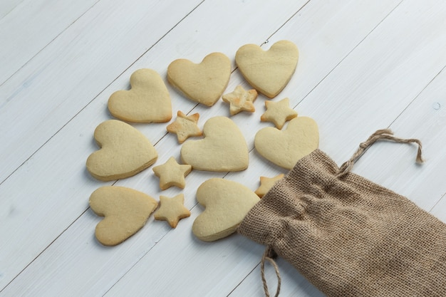 Scattered cookies from a sack on a wooden background. high angle view.