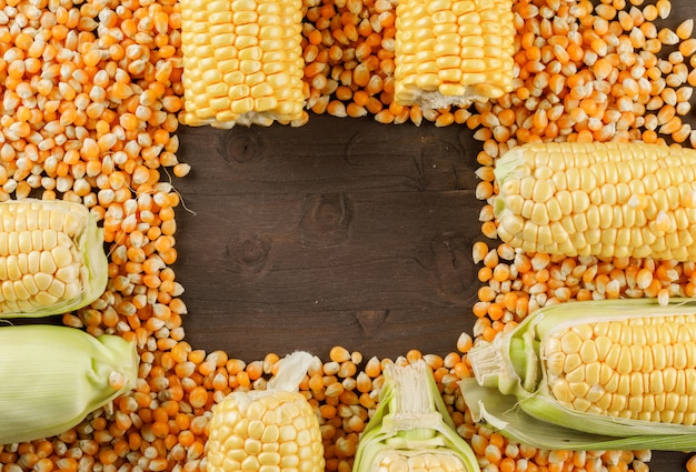 Scattered corn grains with cobs flat lay on a wooden table