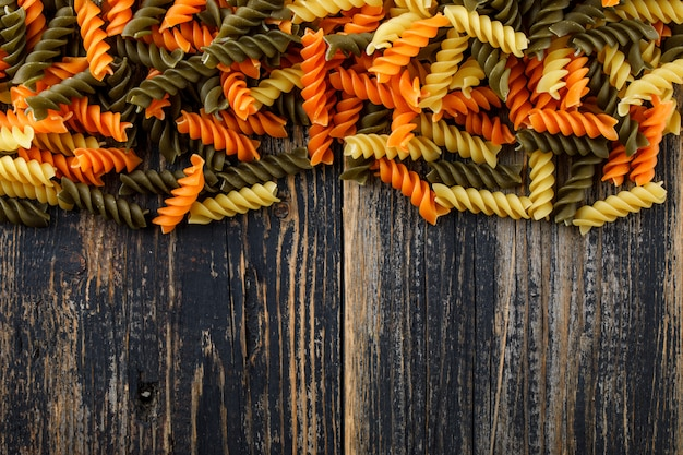 Рассеянные фузилли макароны на старый деревянный стол