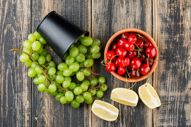 Scattered grapes from a mini bucket with lemon slices, cherries top view on a wooden surface